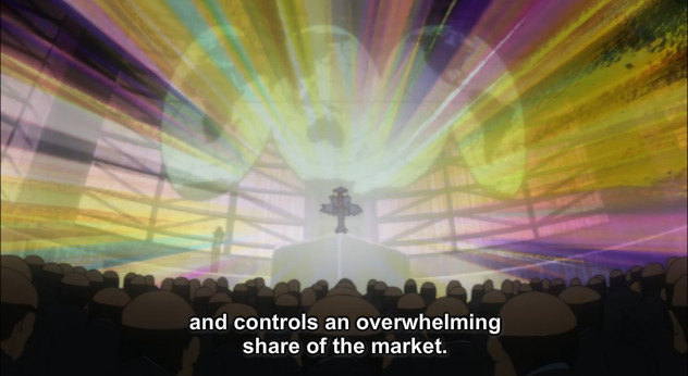 "A screenshot shows Ragyo standing on stage in front of a world map with brilliant light coming out of her. She says, ""and controls an overwhelming share of the market."""