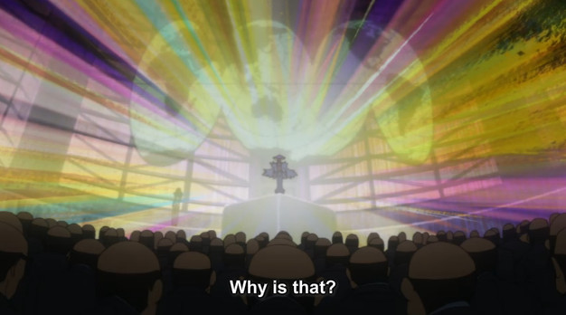 "A screenshot shows Ragyo standing on stage in front of a world map with brilliant light coming out of her. She says, ""Why is that?"""