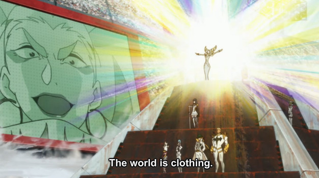 "A screenshot shows Ragyo standing on a podium and addressing the audience. She says, ""The world is clothing."""