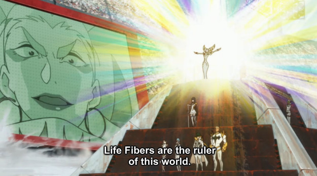 "A screenshot shows Ragyo standing on a podium and addressing the audience. She says, ""Life Fibers are the ruler of this world."""