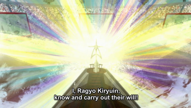 "A screenshot shows a cross structure on a podium with several bright lights shining on it as Ragyo finishes her speech. She says, ""I, Ragyo Kiryuin, know and carry out their will!"""